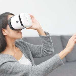 woman holding a virtual reality headset in therapy