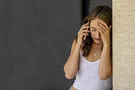 college woman on cell phone depressed
