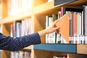 Dr. Estupinian reaching out to a journal in the library