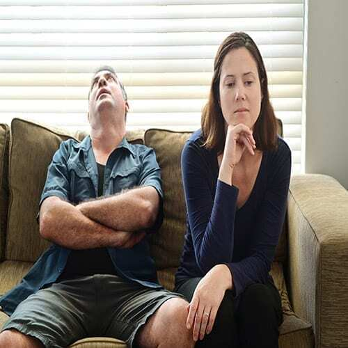 Sad adult couple forced to stay at home as the pandemic coronavirus (COVID-19) forces many people to stay at home because new government policies